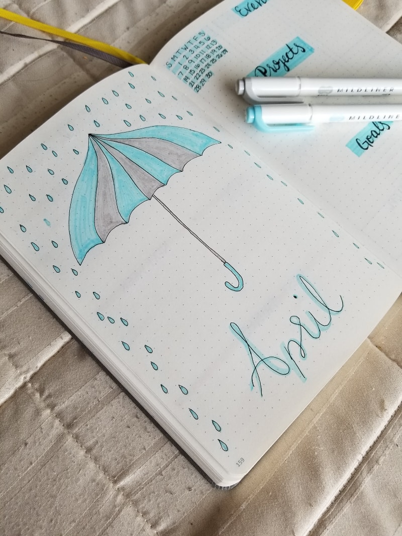 April 2019 Cover Page with blue and grey hand drawn and colored umbrella and rain drops