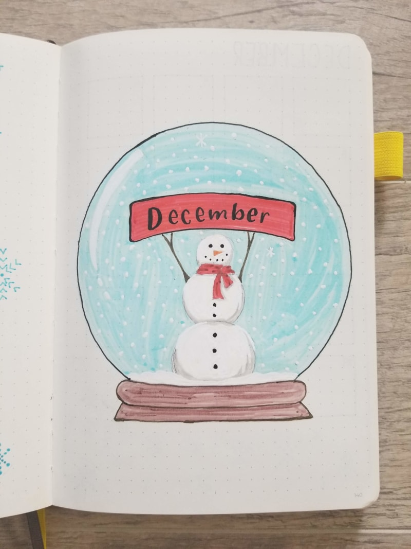 Bullet journal cover page of a snowglobe with a snowman holding up a red banner that says December on it.