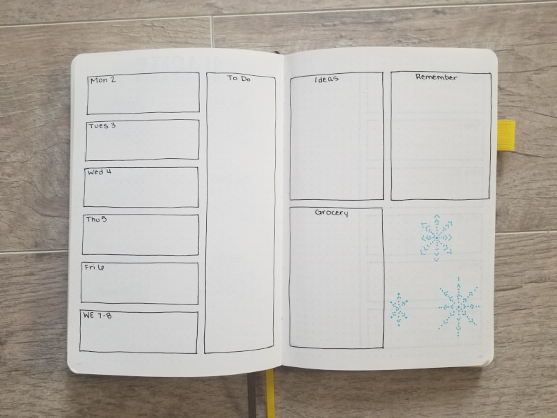 Weekly spread set up for bullet journals with handdrawn snowflakes in the bottom right corner